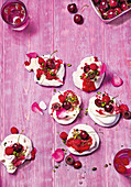 Meringue nests with cream, cherries, raspberries, pistachios and rose petals