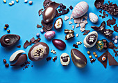 Whole and broken easter eggs on a blue background
