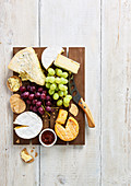 Selection of soft cheeses with biscuits, grapes and chutney on a brown wooden board