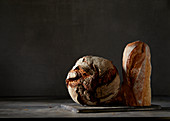 Crusty bread and a baguette in front of a dark background