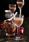 Homemade gingerbread liqueur in a glass with nut-nougat cream spread behind it