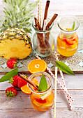 Summer pineapple rum punch with strawberries, mandarins and cinnamon