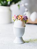 Osterei mit Blumendeko im Eierbecher