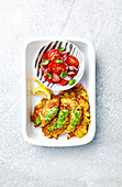 Potato and zucchini fritters served with green pesto and tomato salad