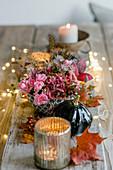 Tischgesteck mit Rosen und Windlichtern