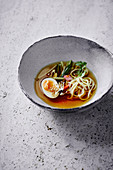 Oriental wheat noodle soup with lemongrass and egg