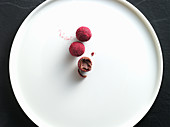 Raspberry truffles on a white plate