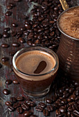 Turkish coffee in a cezve and a glass cup