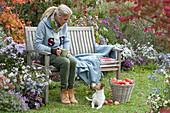 Frau auf Holzbank am Beet mit Herbstastern, Korb mit Äpfeln, Hund Zula
