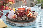 Windlicht auf Schale mit Rosenblüten, Hagebutten und Nüssen