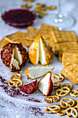 Goat cheese with hot pepper and turmeric and a cracker on a marble pedestal