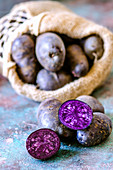 Violette Kartoffeln, ganz und halbiert, mit Jutesack