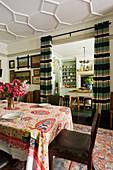 Südafrikanische Tischdecke mit Obama-Motiv auf Esstisch mit Vintage Lederstühlen, Blick durch offenen Vorhängen in die Küche