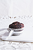 A chocolate muffin in a paper cake with a bow