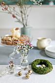 Mooskranz mit Wachteleiern und Frühlingsblüten in Gläsern