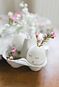 Blüte in ausgeblasenem Ei mit Gesicht