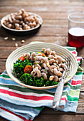 Vegan wholemeal pasta with kale, tomatoes, roasted hazelnuts and cream