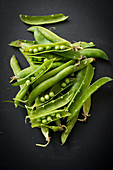 Fresh pea pods on a black background