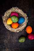 Easter eggs coloured with natural dyes in a nest