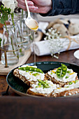 Ricotta toast with peas, lemon zest, and being drizzled with olive oil
