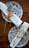 Two place settings with blue and white plates, and white napkins tied with straw and florals