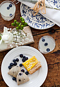 A brunch table with lemonade with blueberries, lemon tart and blueberry scones