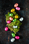 Chocolate eggs wrapped in bright foil surrounding an Easter nest