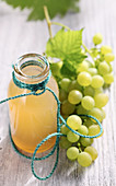 Homemade grape syrup in a glass bottle next to fresh green grapes