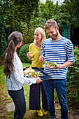 People eating nectarine salad with Parma ham at a BBQ party