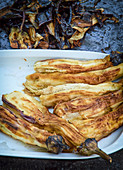 Grilled, skinned aubergines on a plate