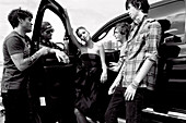 Junge Frau in schwarzem Partykleid und junge Männer in lässigen Outfits am Auto (s-w-Aufnahme)