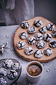 Chocolate crinkle cookies served on a wooden board and ceramic plate in festive Christmas styling