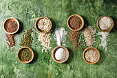 Variety of raw uncooked grains superfood cereal linen seeds, sesame, mung bean, wheat, buckwheat, oatmeal, coconut and rice