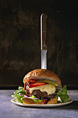 Close up of homemade classic burger in wheat bun with beef and veal cutlets, melted cheese and vegetables