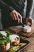 Man's hand cutting cheese on wooden board