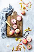 Geschälte und halbierte rosa Äpfel auf Holzschneidebrett