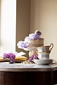 Hochzeitstorte mit Vanillebuttercreme und lila Blumendeko