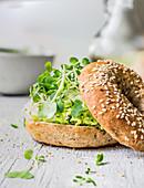 Hausgemachtes Bagel mit Eiersalat, Parmesan und Microgreens