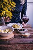 Frau isst Tortelloni mit Käse