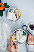 Woman eating savory rice porridge garnished with yogurt, lemon wedges, sumac and dried mint