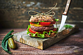 Tasty fresh burger tied with linen thread lying on shabby lumber board