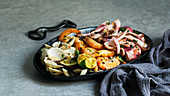 Tasty grilled octopus, oysters and shrimps with lime and herbs on cast iron plate near napkin