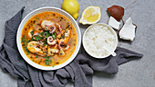 From above bowl of tom yum with shrimps, octopus and herbs near rice, lemon and coconut on grey background