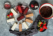 Various small chocolates and cheesecakes with strawberries
