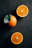 Orangen, ganz und halbiert