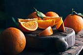 Frische Orangen, ganz und geschnitten, auf Holzkiste