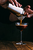 Espresso martini cocktail on dark wooden background