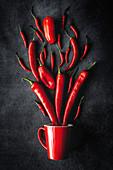 Frische rote und grüne Chilischoten mit Tasse