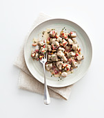 Potato and buckwheat gnocchi with bacon, walnuts and herbs