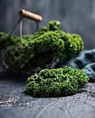 Grünkohl (Brassica oleracea var. sabellica L.) in einem Körbchen und davor